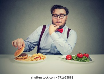Young obese man looking happily at burger with meat instead of healthy salad.