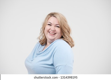 Young obese woman in casual blue clothes on a white background in the studio. Bodypositive and improper nutrition.