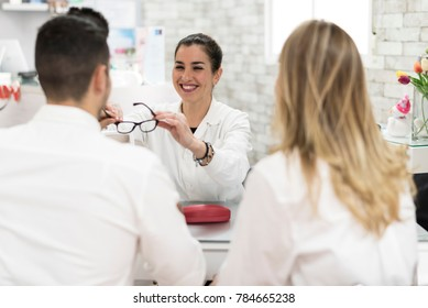 Young oculist woman selling glasses to couple at store
