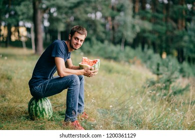 Young odd strange man eating watermelon and drinking its juice at nature. Great delicious taste of summer fruit. Funny adult male fooling with food outdoor in woods. Healthy useful natural  nutrition