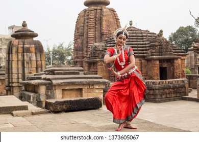 Young odissi dancer striking pose in front of a temple with sculptures in bhubaneswar,odisha