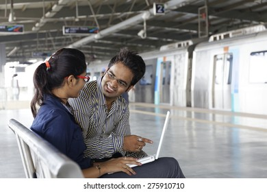 Young office going Indian man and woman sitting on metro station & working on lap top.