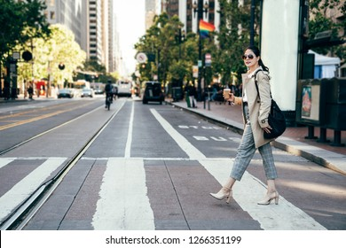 young office lady holding coffee confident walking on road wearing high heels and sunglasses. businesswoman on zebra crossing. rainbow flag hanging on street in background local people riding bike