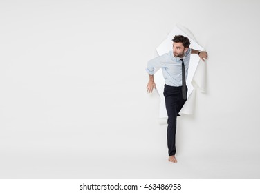 young office man with tie and barefoot breaking the paper background, passing from side to side, looking very curious to one side