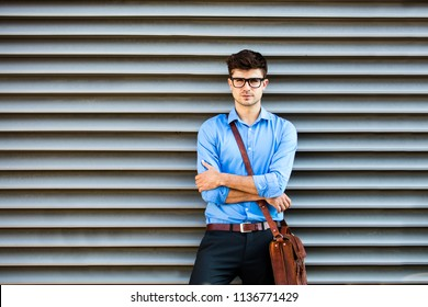 young office man waiting against a wall for something or someone, in office outfit and leather bag, standing against a wall waiting for somene with folded arms