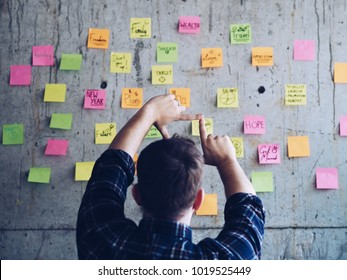 Young office man writing message on post it.