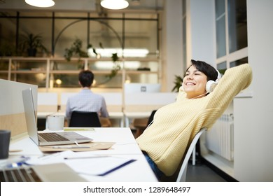 Young office manager with headphones enjoying her favorite music by workplace in front of laptop - Shutterstock ID 1289648497