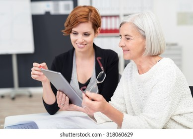 Young Office Woman Teaching her Senior Female Colleague on how to Use Tablet Computer Inside the Workplace.