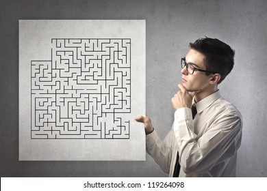 Young office worker holding a cardboard with a drawn maze