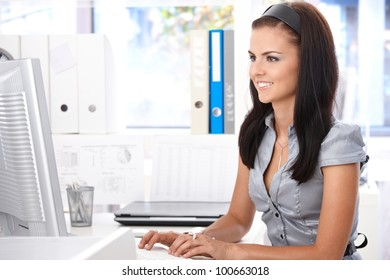 Young office worker sitting at desk, working with computer, smiling.