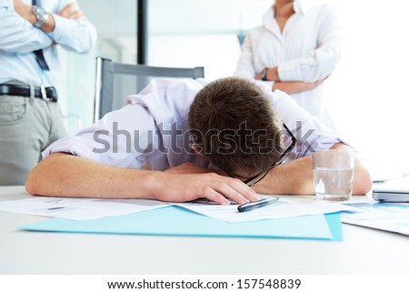 Young office worker is sleeping on the desk, executives behind him