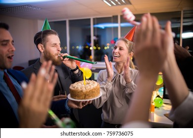 Young office workers congratulating female colleague on birthday, holding cake and blowing party horns