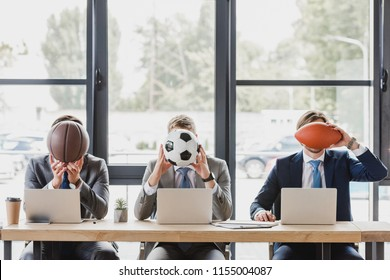 young office workers holding balls while working with laptops in office