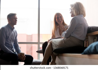 Young office workers interns listening to old woman mentor coach talking to team people at meeting, mature female business leader boss chatting with employees having fun conversation at work break