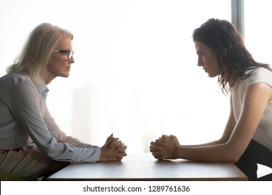 Young and old businesswomen with clasped hands looking at each other sitting opposite as rivalry confrontation concept, female career success envy and jealousy, generations conflict at work concept