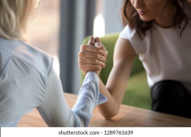 Young and old businesswomen compete arm wrestling fighting for leadership feeling jealous envious about other success, female rivals armwrestling struggling, generations rivalry concept close up view