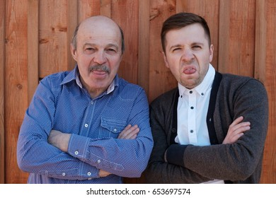 Young and old men show their tongue, fooling around. Funny family portrait.