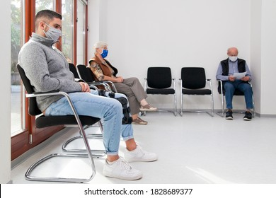 Young and old people with face masks keeping social distance in a waiting room of a hospital or office -  focus on the young man in the foreground