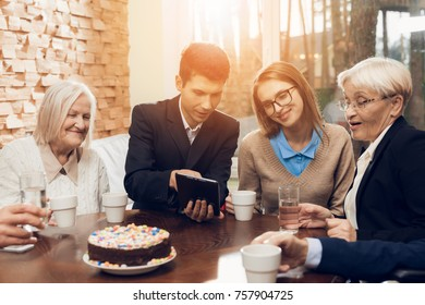Young and old people sit together at the table in the room of a nursing home. They drink different drinks and talk. They are in a good mood. The man is showing something on the tablet.