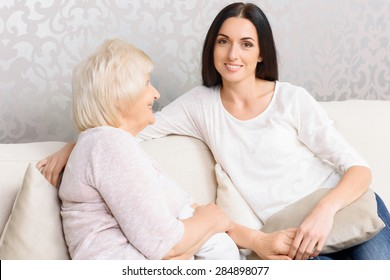 Young and old. Pretty grandmother and her beautiful granddaughter sitting on couch and talking.