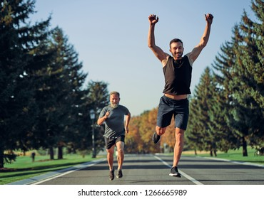 The young and old sportsmen running on the road