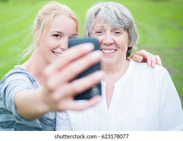 Young and old woman taking a picture with smart phone