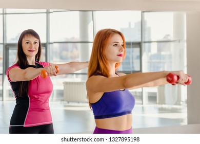 young and older women in sportswear training with dumbbells