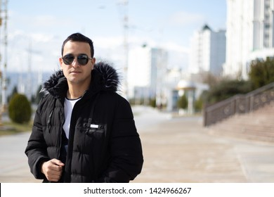a young olive skinned man in a sunglasses in a sunny winter day posing in the capital of Turkmenistan - Ashgabat