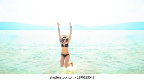 young one woman jumping in ocean at day light. adult girl jump in water on summer beach against blue sky with clouds. Water splash Hair fly in air. Empty space for inscription