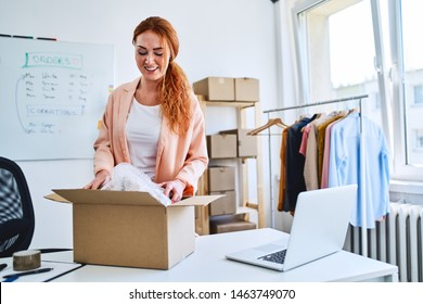 Young online store owner packing delivery into cardboard box in office