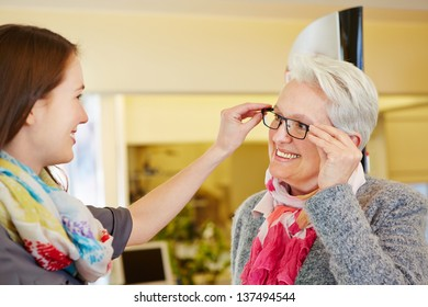 Young optician advising a senior woman for buying new glasses