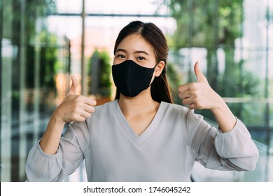Young optimistic Asian female student giving thumbs up gesture. She's wearing a protective mask (PPE) to avoid air pollution or Corona Virus pandemic for safety.