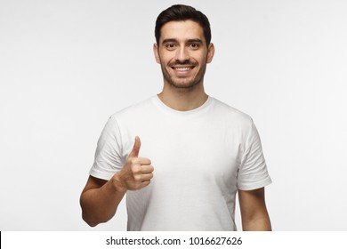 Young optimistic man isolated on grey background showing thump up with positive emotions of content and happiness. Concept of satisfaction with quality and recommendation