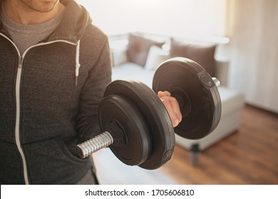 Young ordinary man go in for sport at home. Real picture of not strong guy hold up dumbbells in hand. Trying to do his muscles stronger. Ordinary man with no experience in training. Beginner.