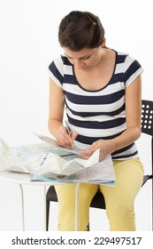 Young organized woman is taking notes for planning a journey - isolated on white