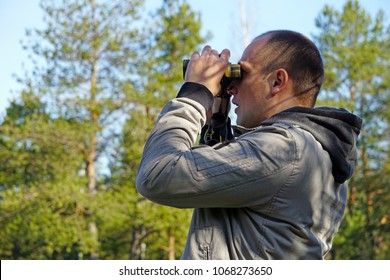 Young ornithologist looking through binoculars in the spring forest at the birds