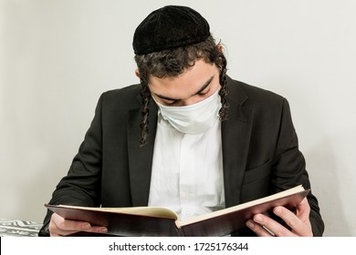 Young orthodox Jew with surgical mask, studying religious texts. Covid-19. global pandemic