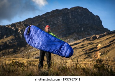 Young outdoor sporty woman posing with sleeping bag in high mountains