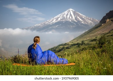Young outdoor woman posing in sleeping bag close by high volcano Damavand, Iran