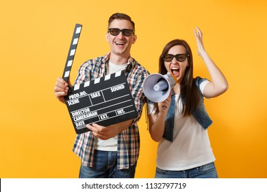 Young overjoyed couple woman man in 3d glasses watching movie film on date hold classic black film making clapperboard screaming on megaphone isolated on yellow background. Emotions in cinema concept