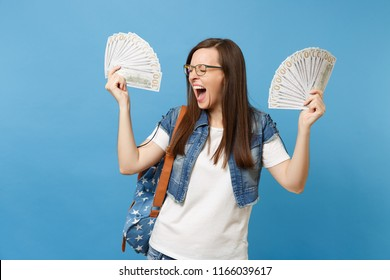 Young overjoyed woman student in glasses with backpack with closed eyes screaming holding bundle lots of dollars, cash money isolated on blue background. Education in high school university college