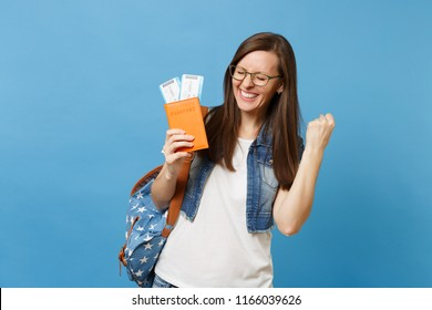 Young overjoyed woman student in glasses with backpack hold passport, boarding pass tickets clenching fist like winner or happy human isolated on blue background. Education abroad. Air travel flight