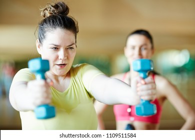 Young overweight female trying hard while exercising with dumbbells with coach on background