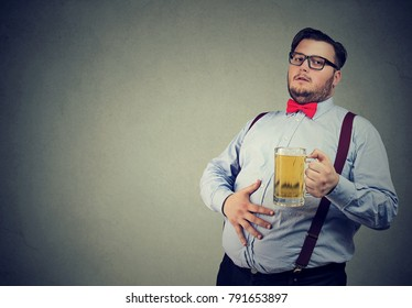 Young overweight man drunk with beer having potbelly.