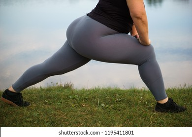 Young overweight woman doing morning yoga, relaxing near lake. Healthy lifestyle, sport, weight losing, activity concept