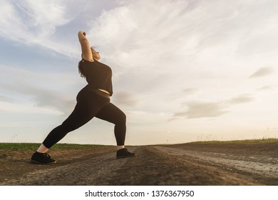 Young overweight woman doing morning yoga on the country road, open air activity. Healthy lifestyle, sport, weight loss