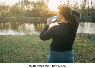 Young overweight woman in sportswear wiping sweat and drinking water after outdoor workout. Healthy lifestyle,hydration, weight losing, activity concept
