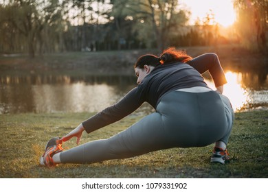 Young overweight woman stretching legs doing morning exercises in the park. Healthy lifestyle, sport, weight losing, activity concept