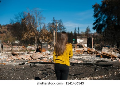 Young owner woman checking burned and ruined house and yard after fire, consequences of fire disaster accident. Ruins after fire disaster, loss and despair concept.