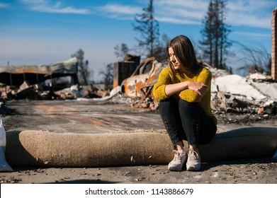 Young owner woman checking burned ruined house and yard after fire, consequences of fire disaster accident. Ruins after fire disaster, loss and despair concept.